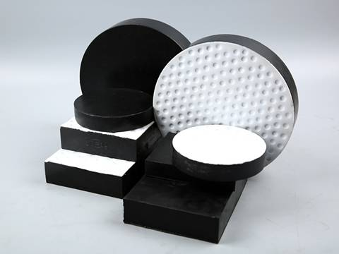 Several round and rectangular standard and Teflon sliding laminated bearing pads on gray background.