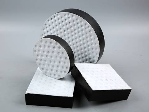 Two round and two rectangular PTFE lamianted bearing pads on gray background.