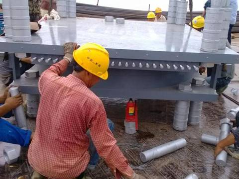 Several workers are installing the spherical bearings in construction site.